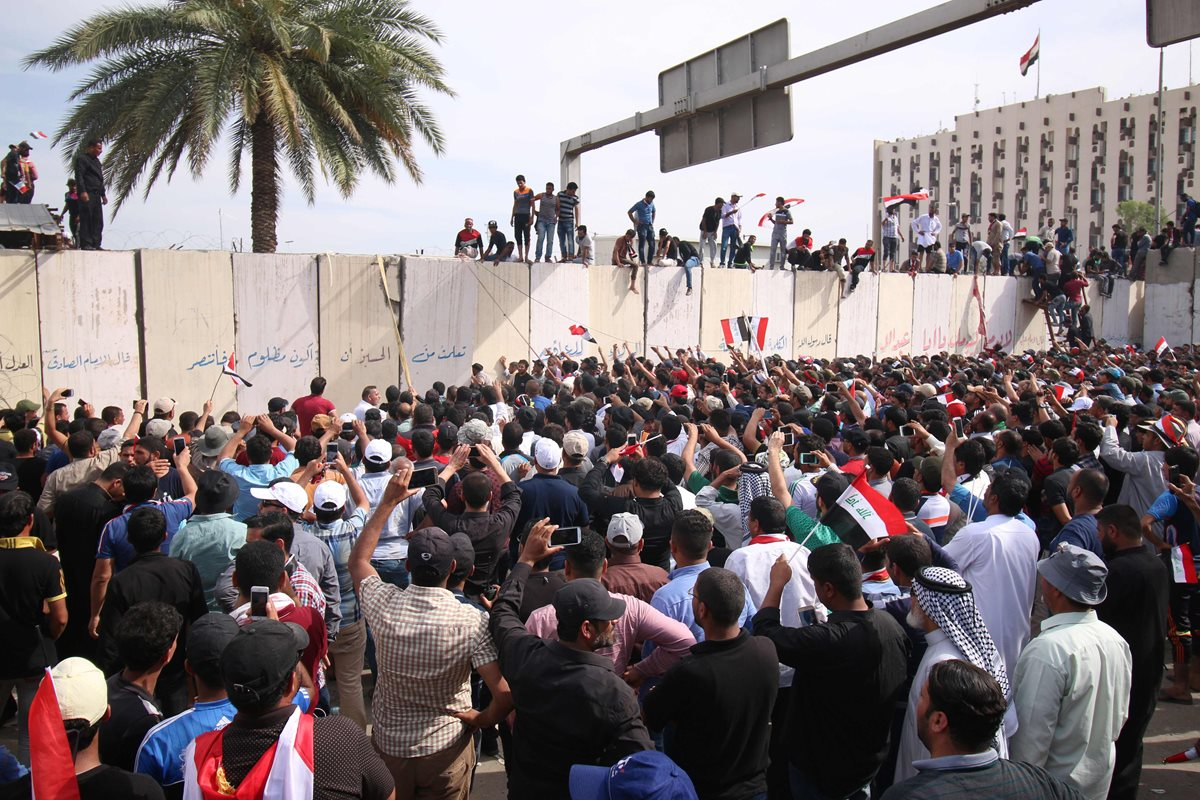 "Iraqi protesters climb over a concrete wall surrounding the parliament (unseen) after breaking into Baghdad's heavily fortified ""Green Zone"" on April 30, 2016. Thousands of angry protesters broke into Baghdad's Green Zone and stormed the parliament building after lawmakers again failed to approve new ministers.Jubilant supporters of cleric Moqtada al-Sadr invaded the main session hall, shouting slogans glorifying their leader and claiming that they had rooted out corruption. / AFP PHOTO / HAIDAR MOHAMMED ALI"