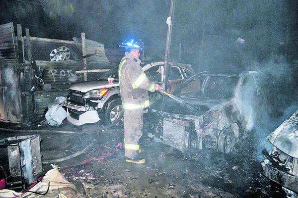 Bomberos trabajan  en apagar un incendio que consumió  ocho vehículos en la zona 4 de Mixco. (Foto Prensa Libre: CVB)