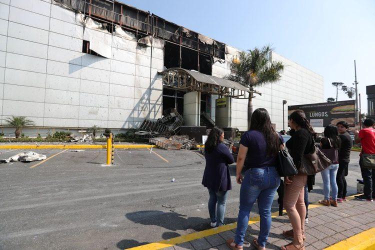 Varios trabajadores del centro comercial y algunos curiosos miraban cómo quedó la fachada del lugar, luego del incendio.