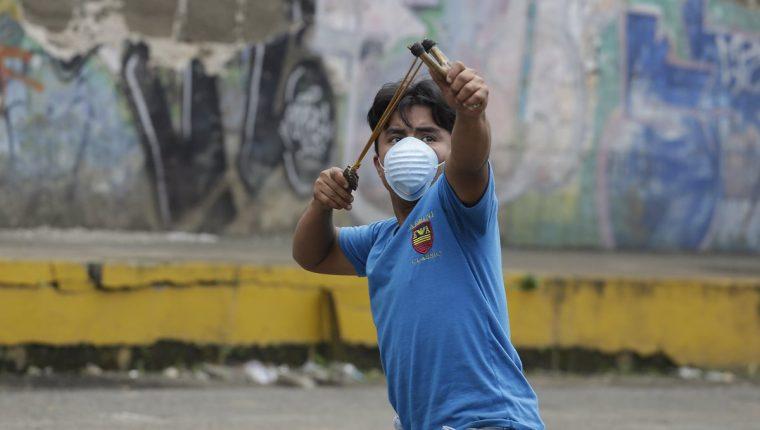 Un joven utiliza una cauchera en el pintoresco pueblo de Jinotepe se convirtió en escenario de guerra.(Foto Prensa Libre:EFE).