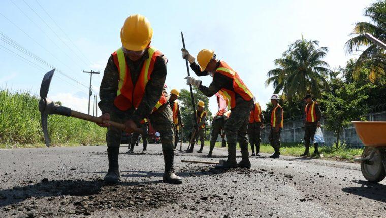 Con piochas, palas y escobas, una brigada del Cuerpo de Ingenieros del Ejército de Guatemala iniciaron las labores de bacheo en la ruta CA2 Suroccidente. (Foto Prensa Libre: Carlos Paredes)