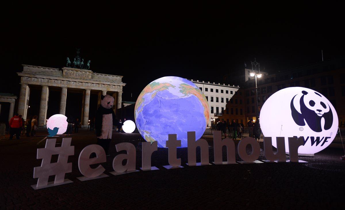 """Un activista de WWF vestido como un oso panda se encuentra junto a un globo iluminado frente a la Puerta de Brandenburger en Berlín durante """"La Hora del Planeta"""". (Foto Prensa Libre:AFP)."""