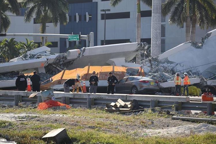 Expertos investigan la escena donde un puente peatonal se derrumbó unos días después de que se construyó en Miami. (AFP).