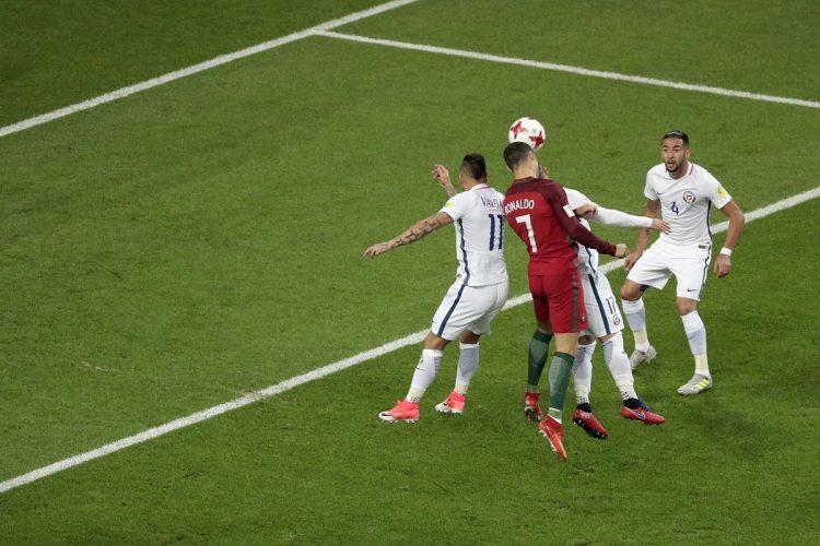 Cristiano Ronaldo cabecea desviado dentro del área en medio de la marca de la defensa chilena.