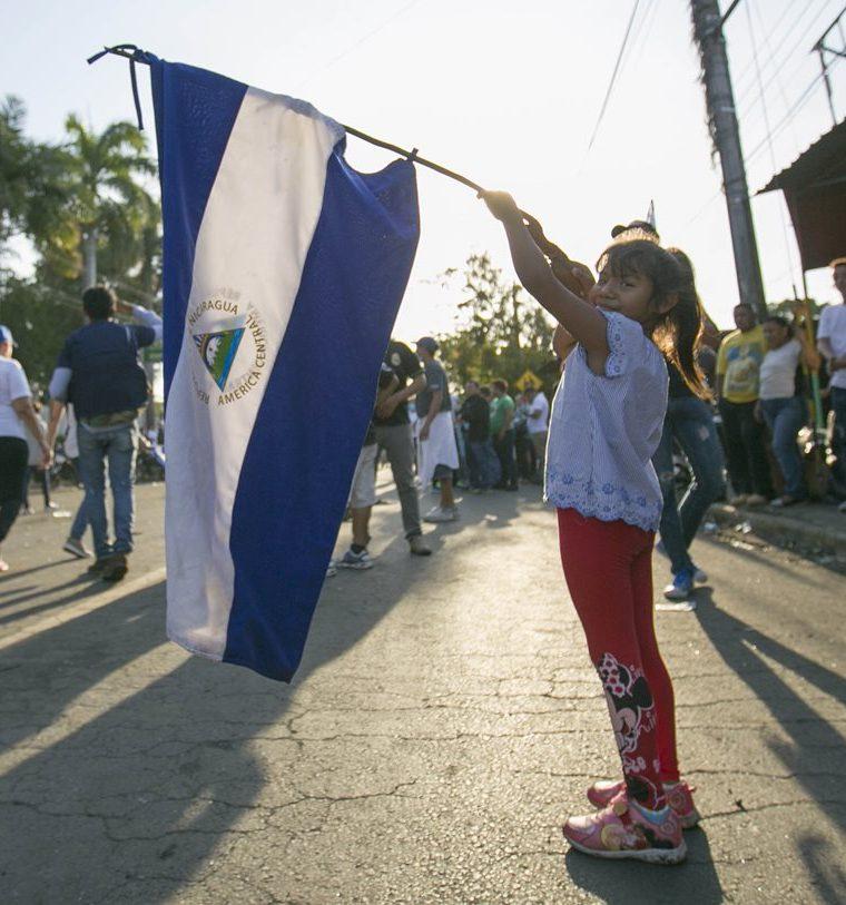Una niña sostiene una bandera de Nicaragua durante la marcha masiva. (Foto Prensa Libre: EFE)