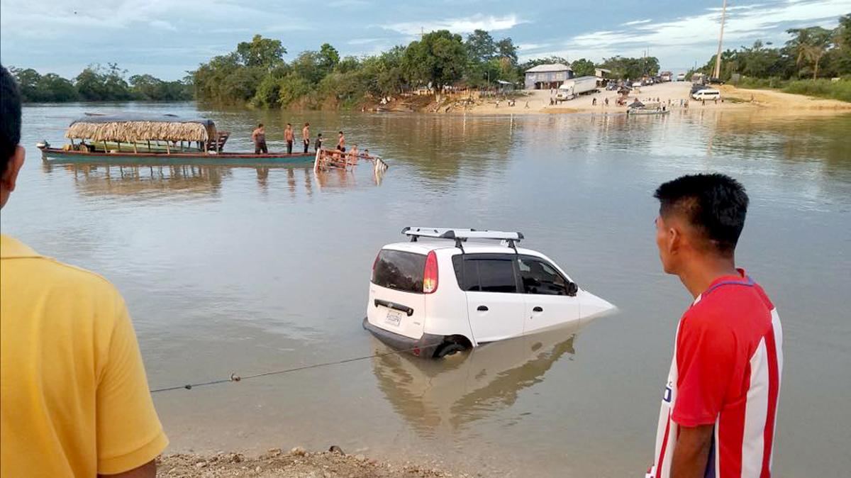 Vecinos sacan del río el taxi en el que viajaban los menores. (Foto Prensa Libre: Dony Stewart).