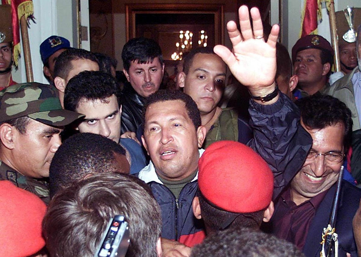 Hugo Chávez saluda a sus camaradas a su llegada al Palacio de Miraflores para reasumir al poder. (Foto: AFP)