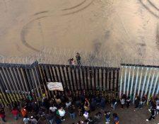 Migrantes observan hacia territorio estadounidense desde la frontera de Tijuana, México. (Foto Prensa Libre: AFP)