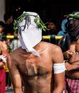 Penitentes se fustigan mientras caminan en procesión hacia una iglesia con el rostro cubierto durante las celebraciones del Jueves Santo en San Pedro Cutud, Filipinas. (Foto Prensa Libre: EFE)