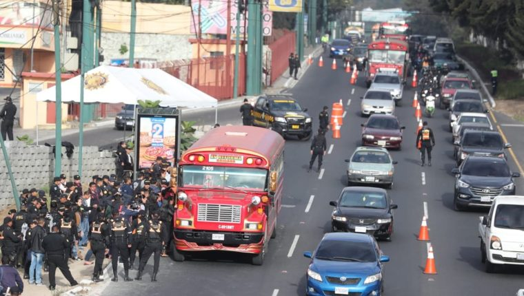 Los pasajeros de autobuses que transitan en las calzadas San Juan y Roosevelt descienden de las unidades para ser revisados por agentes de la PNC. (Foto Prensa Libre: Érick Ávila)