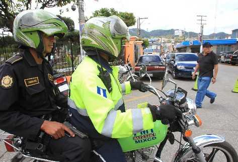 Un agente  de la Policía Nacional Civil patrulla las calles de Mixco con apoyo de un agente de Tránsito.