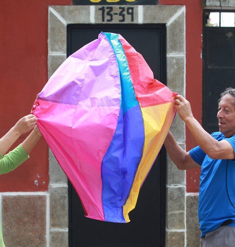 Con ayuda de su esposa, Marco Antonio Chacón extiende uno de los globos más pequeños que elabora. (Foto Prensa Libre: Estuardo Paredes)