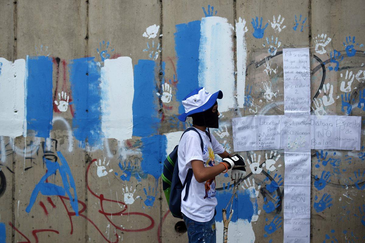 Un nicaragüense enmascarado participa en una vigilia para conmemorar los 100 días de protestas contra Ortega. (AFP)