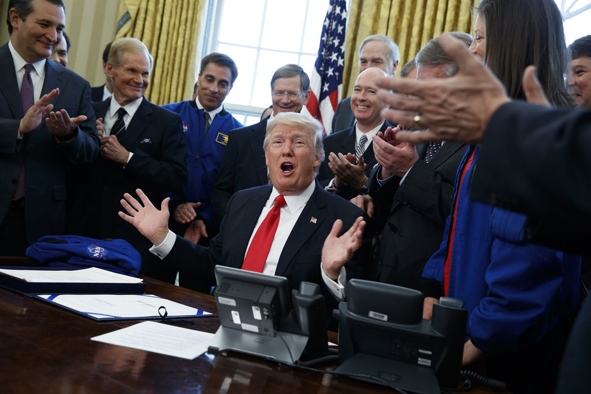 Funcioanarios celebran después de que Trump firma incremento de presupuesto para la Nasa. (Foto Prensa Libre: AP)