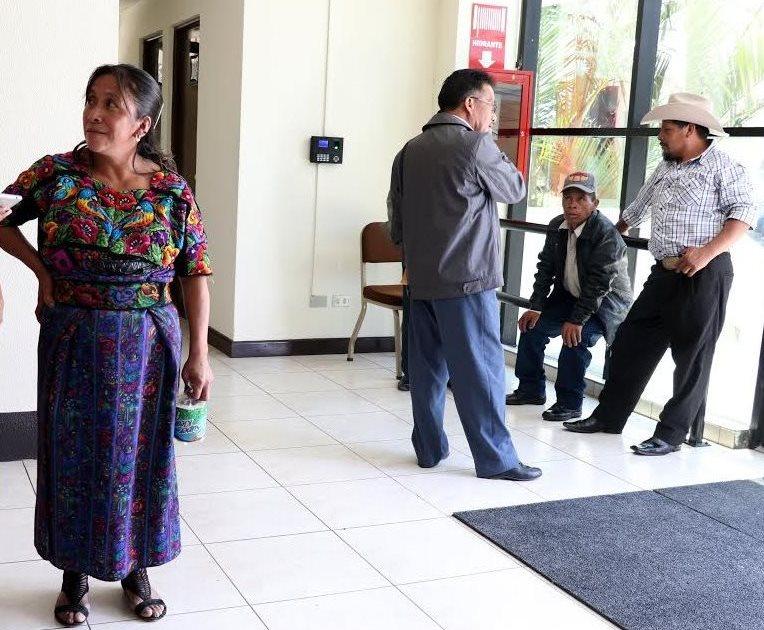 La vendedora Eulalia Alonzo y Carlos Félix, alcalde de San Rafael La Independencia (chumpa gris), asisten a la audiencia en el Juzgado de Primera Instancia de Santa Eulalia. (Foto Prensa Libre: Mike Castillo)