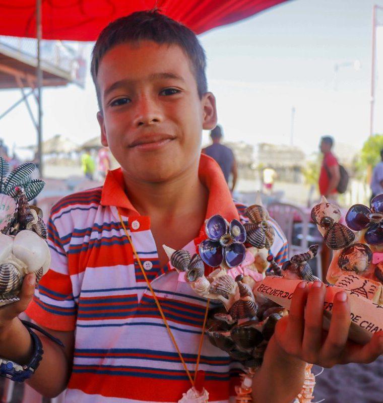 Niño muestra algunas de las artesanías que los visitantes encontrarán en Champerico. (Foto Prensa Libre: Rolando Miranda).