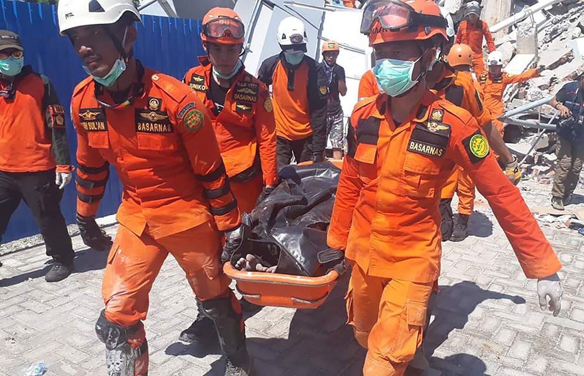 Rescatistas llevan un cuerpo que fue localizado entre los escombros de un edificio en Palu. (Foto Prensa Libre: AFP).