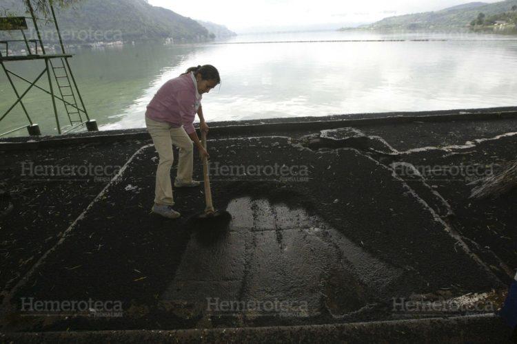 Una persona limpia de ceniza un chalet en la orilla del Lago de Amatitlán.
