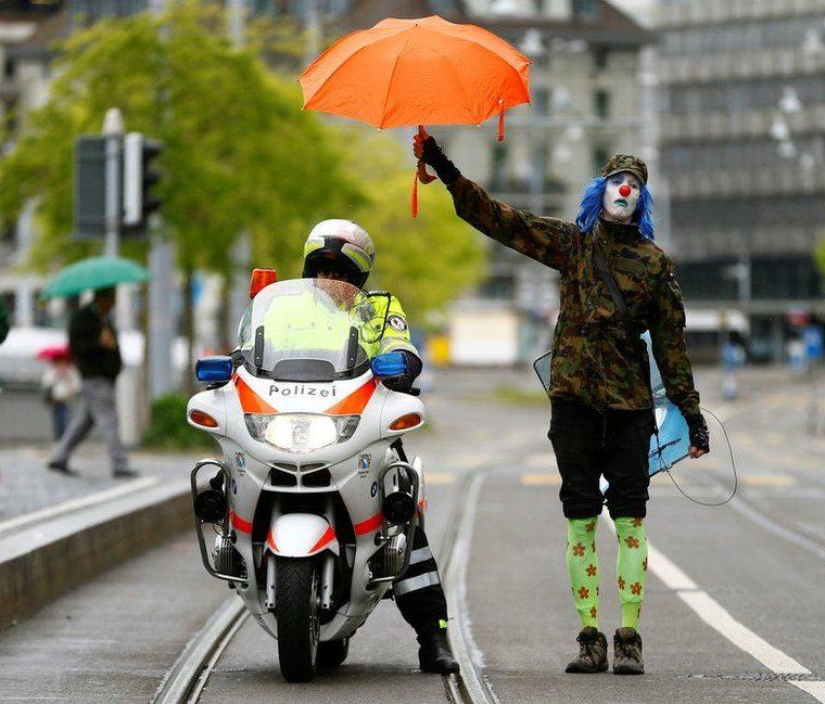Un manifestante vestido de payaso cubre a un policía con su paraguas durante las protestas del 1 de Mayo en Zurich, Suiza. ARND WIEGMANN / REUTERS