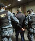 Agentes antinarcóticos trasladan a Tribunales a Julio César Orellana Cordón luego de capturarlo en el Aeropuerto Internacional La Aurora. (Foto Prensa Libre: PNC).