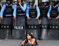 Una manifestantes se acuesta frente a la policía en una protesta contra la reelección del presidente Juan Orlando Hernández en Honduras. GETTY IMAGES