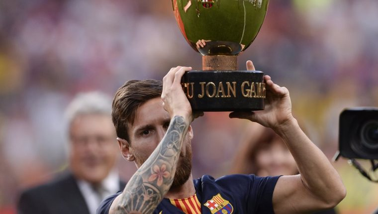 Lionel Messi levanta el Trofeo Joan Gamper. El argentino anotó el segundo gol del partido. (Foto Prensa Libre: AFP)
