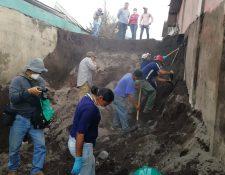 Damnificados y socorristas guían al operario de una máquina retroexcavadora que remueve arena volcánica en el callejón principal de San Miguel Los Lotes, El Rodeo, Escuintla. (Foto Prensa Libre: Carlos Paredes)