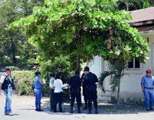 Fiscales del  Ministerio Público examinan la escena del crimen, donde una mujer murió baleada y un hombre resultó con heridas graves, en Puerto San José, Escuintla. (Foto Prensa Libre: Carlos Enrique Paredes)