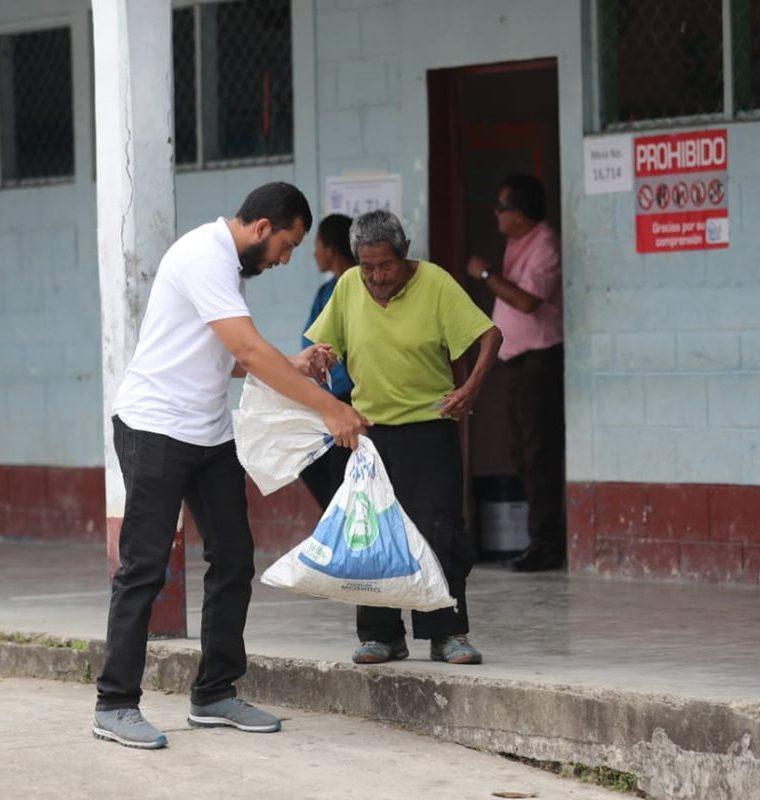 Henrry Pocasangre, enviado especial de Prensa Libre, apoya a don Magdaleno Chún al momento de salir del centro de votación en San Luis Petén. (Foto Prensa Libre: Érick Ávila)