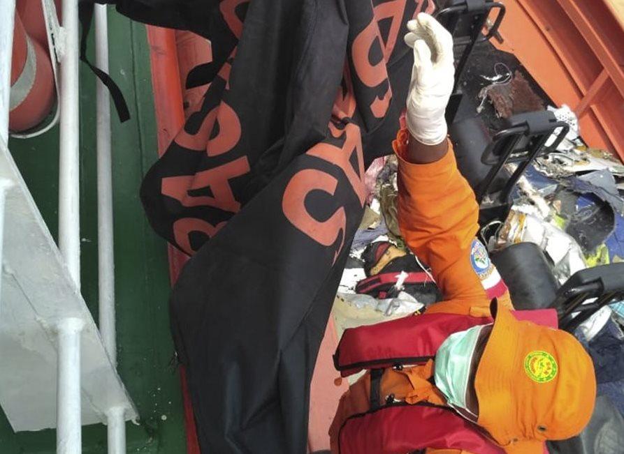 Un socorrista ayuda a rescatar los restos de una de las víctimas del accidente aéreo que se precipitó a gran velocidad al mar de Java. (Foto Prensa Libre: EFE)