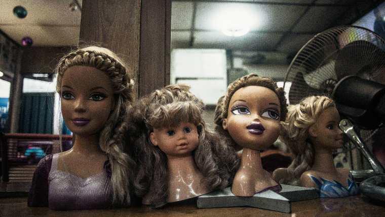 Una peluquería muestra cabezas de muñecas para peinar el cabello en un en el centro de San Salvador, El Salvador. (Foto Prensa Libre:AP)