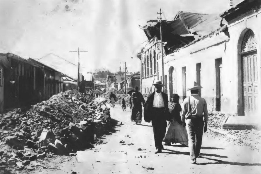 Aspecto de la 5ª. avenida y 17 calle de la zona 1 después de los sismos que hace un siglo destruyeron la ciudad de Guatemala. Al fondo se aprecia el Castillo de San José, hoy Museo Militar.