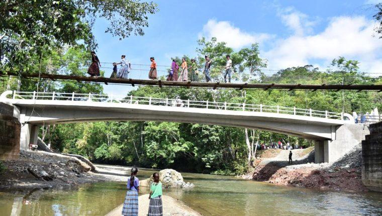 Un grupo de pobladores cruzan el antiguo puente de hamaca mientras que otro permanece sobre la nueva estructura, en la comunidad q'eqchi' Nimlabenqué, El Estor, Izabal. (Foto Prensa Libre: Dony Stewart)