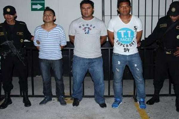 Agentes custodian a los tres hombres capturados. (Foto Prensa Libre: PNC)