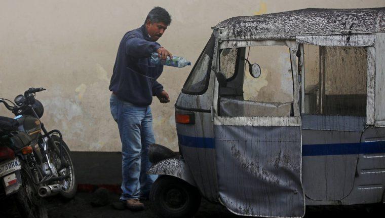 Un hombre limpia su mototaxi de ceniza del volcán de Fuego en Antigua Guatemala, Sacatepéquez (Guatemala) (Foto Prensa Libre: EFE).
