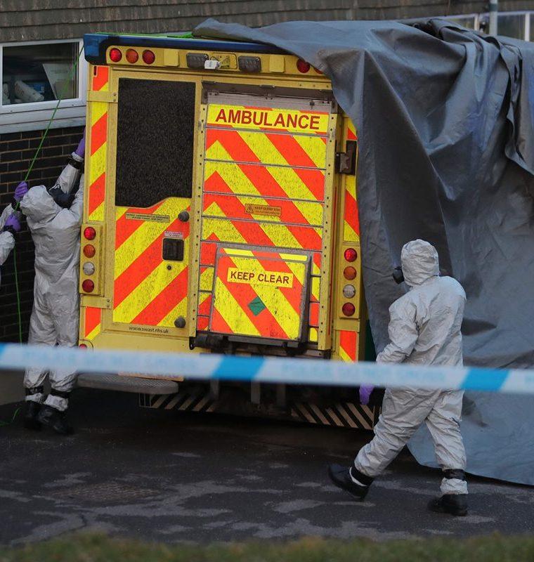 Efectivos de seguridad cubren una ambulancia con una lona alquitranada para ser retirada por personal militar en el Hospital Salisbury District en Salisbury, sur de Inglaterra. (AFP).