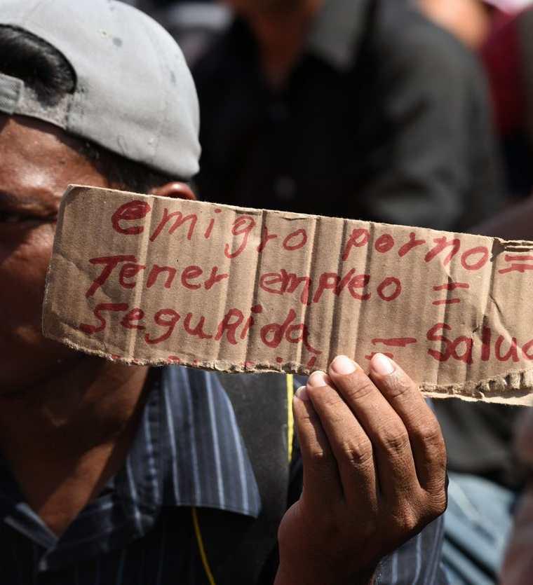 Migrante hondureño muestra un cartel que explica las razones de su migración, entre ellas falta de empleo, salud y seguridad. (Foto Prensa Libre: AFP)