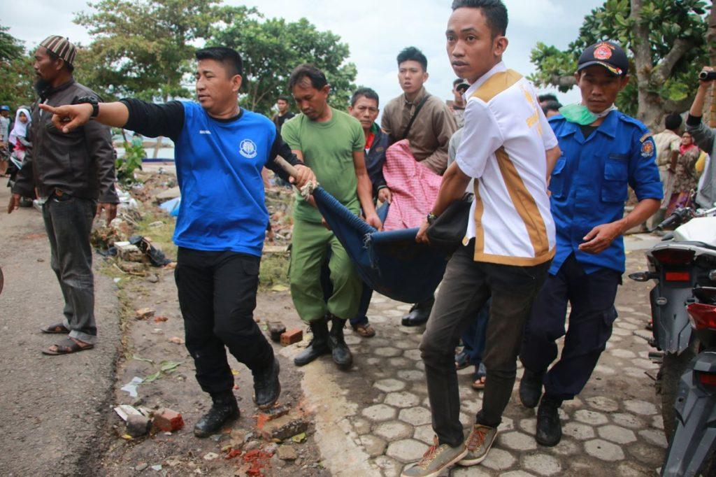 Voluntarios rescatan varios cadáveres de víctimas tras el impacto del tsunami en Indonesia.