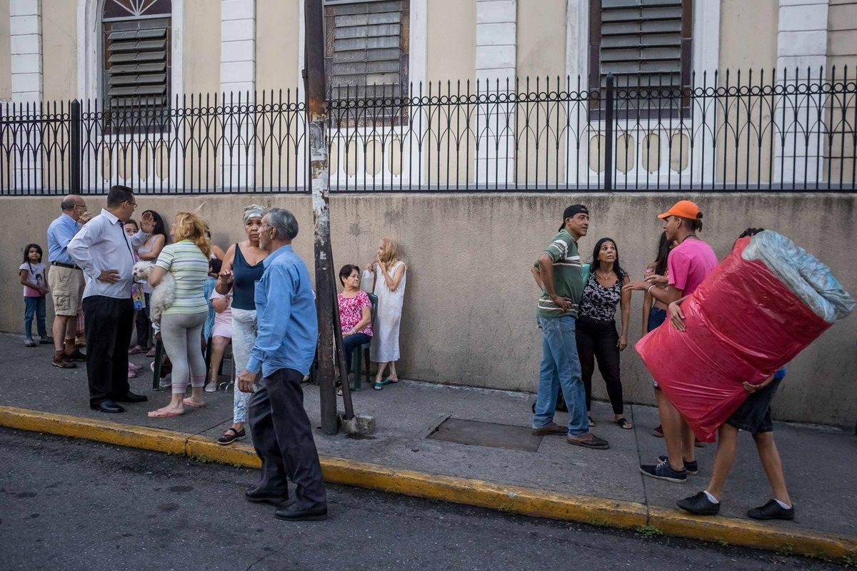 """CR008. CARACAS (VENEZUELA), 21/08/2018.- Un grupo de personas permanece en la calle luego de que se registrara un sismo hoy, martes 21 de agosto de 2018, en Caracas (Venezuela). Los venezolanos se vieron hoy estremecidos por un fuerte sismo de magnitud 6,3 con epicentro en el """"sureste de Yaguarapano"""" en el oriente del país, de acuerdo con la Fundación Venezolana de Investigaciones Sismológicas (Funvisis), aunque el Servicio Geológico de EE.UU. reporta una magnitud de 7,0. EFE/Miguel Gutiérrez"""