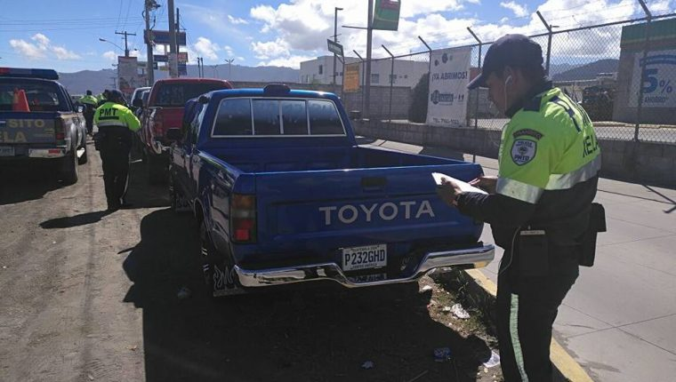 Un agente de la Policía de Tránsito de Xela impone una multa al conductor de un picop por parquearse en un lugar prohibido en la zona 7. (Foto Prensa Libre: PMTQ)