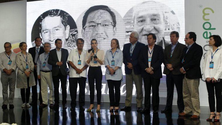 La periodista ecuatoriana Gabriela Vivanco (c) del diario La Hora, donde denuncia la muerte de tres periodistas (al fondo), durante la reunión de la SIP. (Foto Prensa Libre: EFE)
