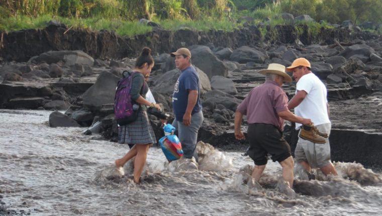 Vecinos arriesgan la vida al cruzar un río crecido por las constantes lluvias en San Pedro Yepocapa. (Foto Prensa Libre: Víctor Chamalé).