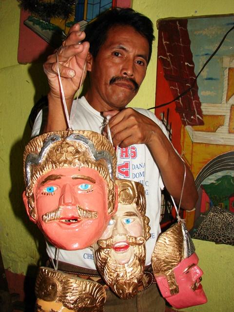 El artesano Miguel Macario posa con varias máscaras que son de su creación. (Foto Prensa Libre: Cristian I. Soto)