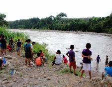 Curiosos observan el cadáver que estaba flotando en el río Ocosito, Nuevo San Carlos, Retalhuleu. (Foto Prensa Libre:Rolando Miranda)