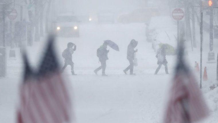 Personas en Nueva Jersey cruzan una calle completamente cubierta por la nieve. (Foto Prensa Libre: AP)