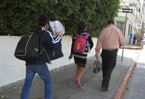 Julio López, de Malacatán, San Marcos, lleva a sus hijos, quienes el lunes fueron deportados de México. Los menores pasaron la noche en un albergue.