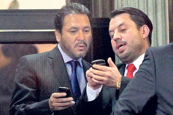 Gudy Rivera, del PP y expresidente del Congreso, y Salvador Baldizón, de Líder, revisan información.