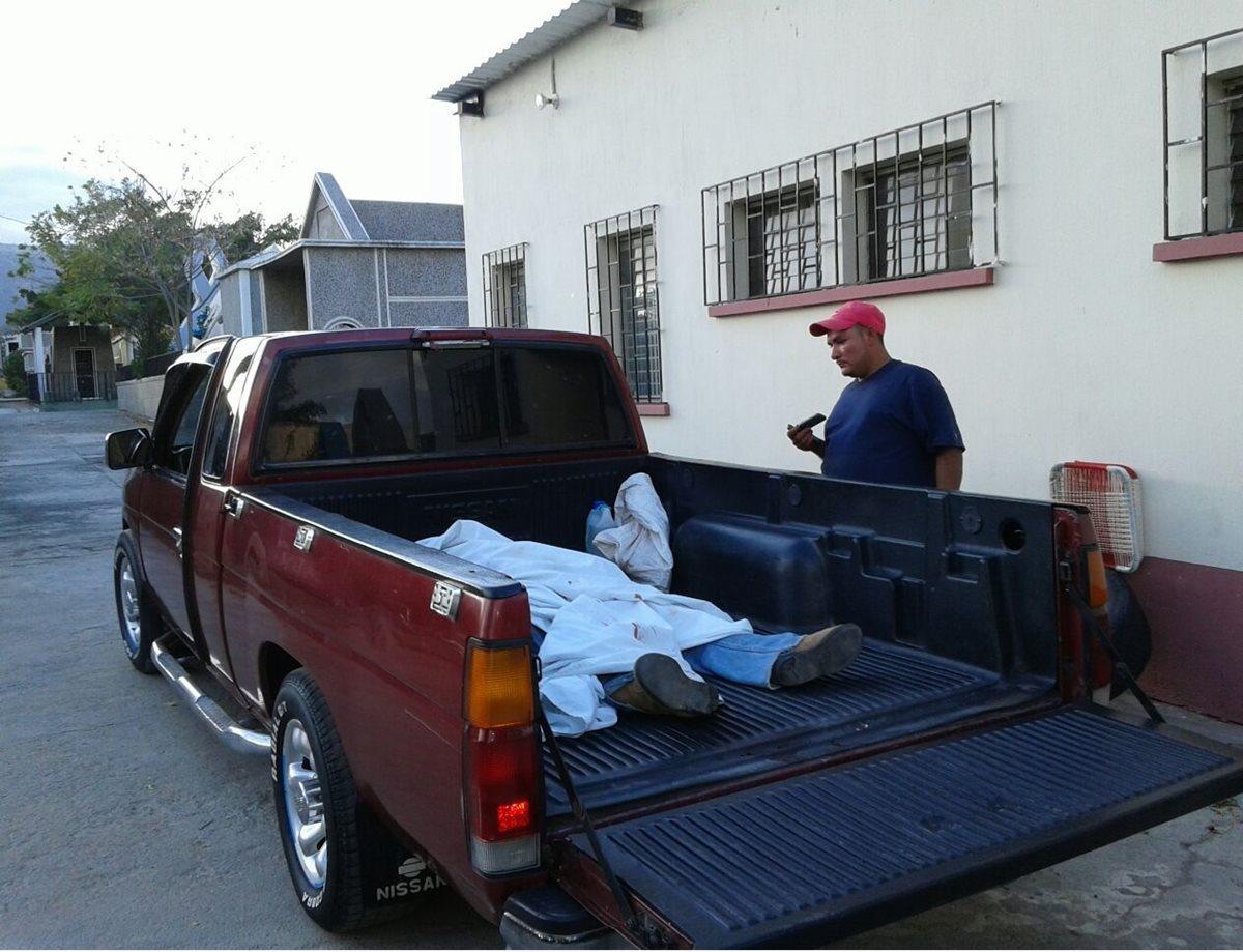 El cadáver es trasladado en un picop particular frente a la morgue del Instituto Nacional de Ciencias Forenses de Chiquimula. (Foto Prensa Libre: Edwin Paxtor)