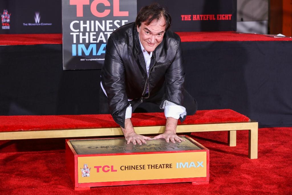 Quentin Tarantino coloca sus manos en el cemento durante una ceremonia en el teatro chino de Hollywood. (Foto Prensa Libre: AP)