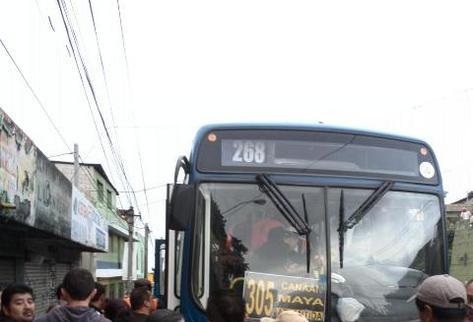 Algunos curiosos observan el lugar del ataque ocurrido en contra de pasajeros de Transurbano con ruta a colonia Maya, zona 18. Foto Prensa Libre: Claudia Galán).